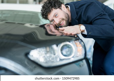 Visiting car dealership. Handsome bearded man stroking his new car and smiling