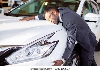 Visiting car dealership. Handsome black man is hugging his new car and smiling