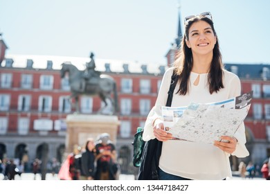Visiting famous landmarks and places.Cheerful female traveler at famous Plaza Mayor square admiring statue of Philip III.Spain travel experience. Backpacker in Madrid.