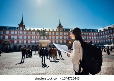 Visiting famous landmarks and places.Cheerful female traveler at famous Plaza Mayor square reading a map. Marid,Spain travel experience. Backpacker, travel photography.