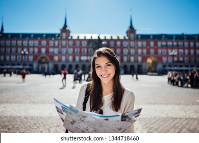 Visiting famous landmarks and places.Cheerful female traveler at famous Plaza Mayor square reading a map. Marid,Spain travel experience.