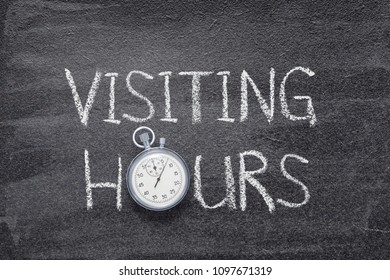 visiting hours phrase handwritten on chalkboard with vintage precise stopwatch used instead of O