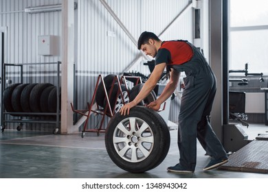Visiting the showroom. Mechanic holding a tire at the repair garage. Replacement of winter and summer tires.