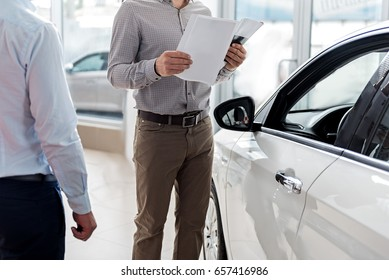 Visitor looking through agreement in car dealership