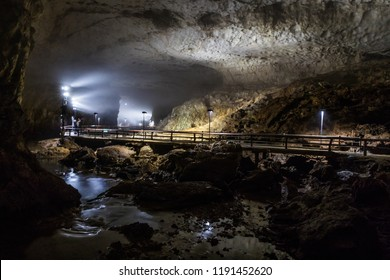 The visitor path bridges the river and the Hundred Plates (Hyakumaizara) rimstone dam formation in a large hall of Akiyoshi Cave in Yamaguchi Prefecture, Japan