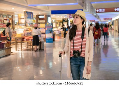 visitor standing in the airport. duty-free shops in Taipei International Airport.