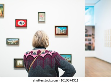 Visitor standing in front of white wall with artworks in museum room. Rear view.
