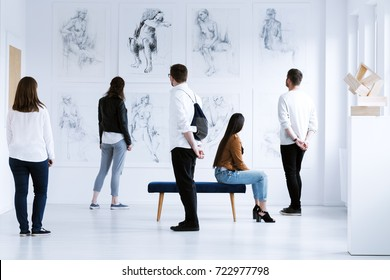 Visitors in art gallery with drawings and sculpture during cultural meeting. Art gallery concept