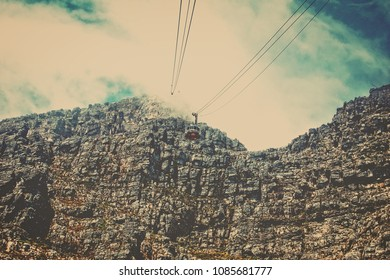 Visitors climb up to the top of a mountain with a help of a cable way. Retro. Wonderful vintage of mountain nature. Up in the clouds. Stunning view of a mountain top. Matte