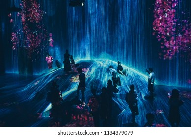 Visitors enjoying the 'rain' in one of the spaces within teamLab permanent exhibition in Mori Digital Art Museum. Picture taken in Tokyo, Japan on 14 July 2018.