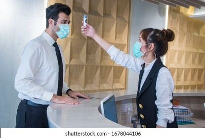 Visitors must go through fever measures using infrared digital thermometer check temperature measurement, fever examination at the building.Measures to prevent people with fever, Covid 19 concept