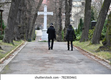Visitors on a cemetery in Berlin. They are walking to a white Christian cross.