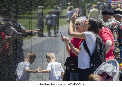 Visitors photograph names on the wall of the Vietnam Veterans Memorial, Washington DC.