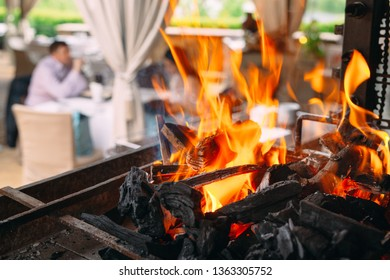 Visitors to the restaurant on the background of a burning grill