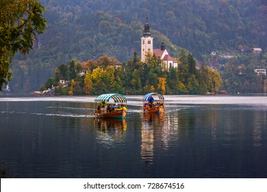 Visitors returning on boats from the old chuch in Lake Bled island on a rainy autumn day