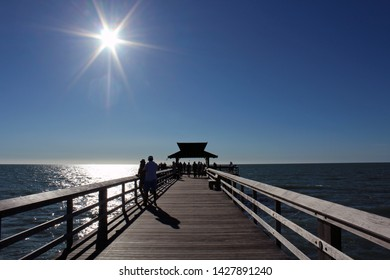 Visitors stand on landmark The Pier in Naples FL, popular for exquisite sunsets and boatless fishing, as blazing sun begins to set in the cloudless blue sky. Gulf of Mexico.