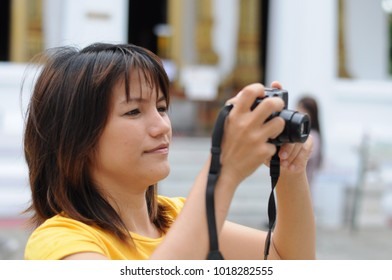 Visitors are taking photos in a temple in Thailand.