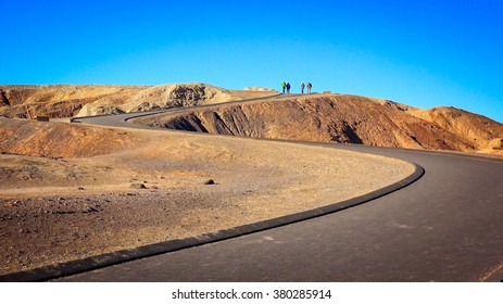 Visitors at the top of a winding path leading to Zabriskie Point in Death Valley National Park