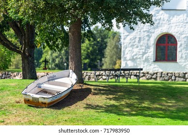 Vissefjarda, Sweden - August 28, 2017: Environmental documentary of the village church and surrounding area. Small rowboat tied to a tree outside the church.