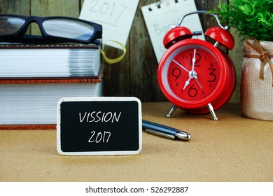 VISSION 2017 inscription written on chalkboard. Red alarm clock, books, spectacle, notes at background.