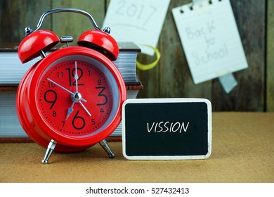 VISSION inscription written on chalkboard, red alarm clock, books on desk. Notes and old wooden background. Time concept.