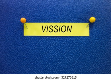 A VISSION wording on the yellow stick note pinned on the blue board, information concept.