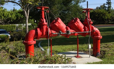 Vista, CA / USA - August 31, 2018: A bright red double-check back flow preventer with metered bypass valve on a water main