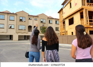 Vista, CA / USA - October 6, 2018: A mother and her teen daughters looking at newly built townhomes for sale