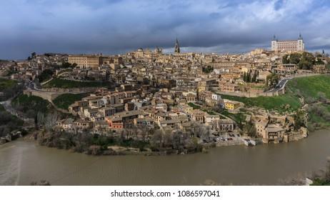 Vista panorâmica da cidade de Toledo, na Espanha, com o Alcazar à direita, torre da catedral no centro superior e do rio Tejo em torno da cidade em uma tarde de inverno