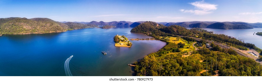 Vista of Hawkesbury river near Pacific Motorway Sydney-newcastle in wide aerial panorama of underneath coast, hill ranges; woods, towns, boats and infrastructure on a sunny summer day.