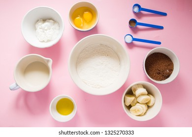 Visual guide made of single photo showing the different step to prepare a banana bread, ingredients to prepare the bread , eggs, flour, sugar, grreek yogurt, oil  and butter, and banana,are displayed