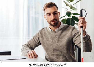 Visually impaired man in wireless earphones holding walking stick at table