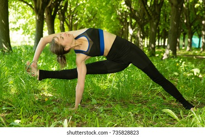 Visvamitrasana. Beautiful young woman doing stretching exercise on green grass at park. Yoga. Concept of healthy lifestyle and relaxation. Young yoga teacher practicing outdoors in a park