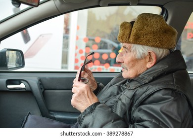 Vital elderly man with fur hat  sitting in a car, holding eyeglasses during drive