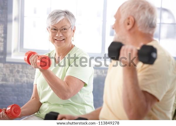 Vital senior couple exercising in the gym.