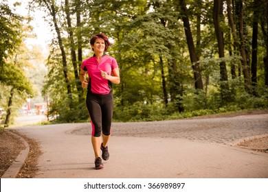 Vital senior woman jogging in park on summer evening