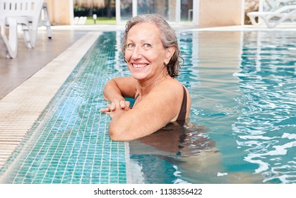 Vital senior woman at the poolside in a swimming pool or spa hotel
