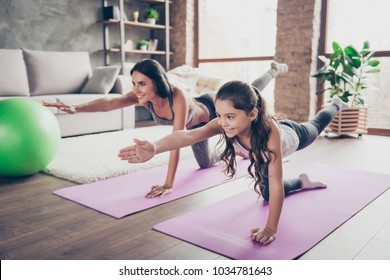 Vitality concept. Watch repeat the moves, poses from the helpful video! Cute sweet cheerful joyful with long hair schoolgirl and slim sportive mom are doing stretching exercises in room om purple mats