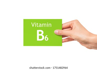 Vitamin B6. Female hand shows a card with the inscription Vitamin B6.