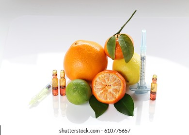 Vitamin C in ampoules, two syringes, , lemon,  orange and lime on a light background. Organic Cosmetics Concept