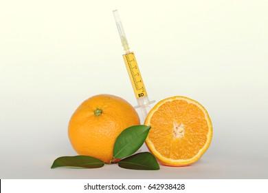 Vitamin C (ascorbic acid) concept. Orange in a cut and a syringe with vitamin C