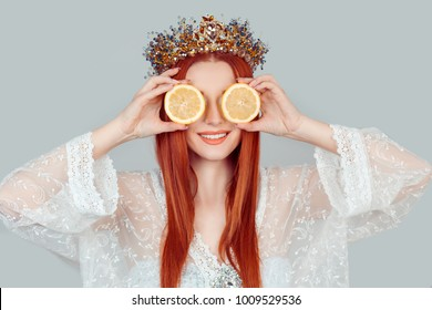 Vitamin C and beauty. A young woman holding covering eyes with two slices of orange lemons as a eye area skin mask pretty woman with crystal crown on head isolated on light gray background wall