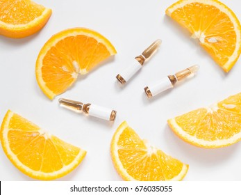 Vitamin C brown ampule for injection with fresh juicy orange fruit slides on white table. High dose vitamin c synthetic for white skin. Beauty product branding mock-up. Healthy lifestyle. Top view.