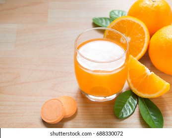 Vitamin c effervescent tablet is dissolving in glass of water w/ bubbles and fresh juicy orange fruits on wood table. Vitamin/mineral supplement, nutrition, health care and medical. Copy space.