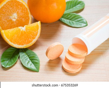 Vitamin c effervescent tablet spilling out of white plastic bottle with fresh juicy orange fruits and green leaf on wood table. Vitamins from foods or supplements choices. Health and medical concept.