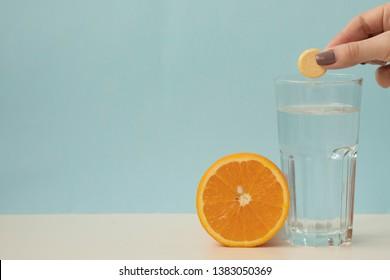 vitamin C family, orange, tablet stack, dissolving tablet. Effervescent vitamin C tablet bubbles in glass of water