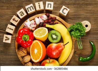 Vitamina C en frutas y verduras. Productos naturales ricos en vitamina C como naranjas, limones, frutas secas rosa, pimienta roja, kiwi, hojas de perejil, ajo, bananas, peras, manzanas, nueces, ají.
