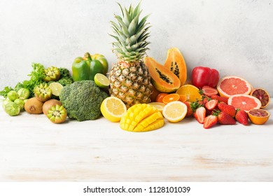 Vitamin C fruits and vegetables in rainbow colors, oranges mango grapefruit kiwi kale pepper pineapple lemon papaya broccoli, on white table, copy space for text in the bottom, selective focus