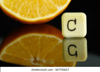 Vitamin C and lemon with reflection in black