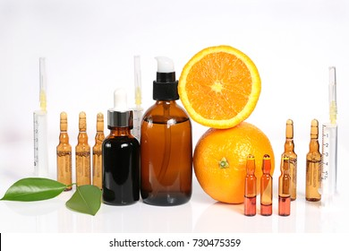 Vitamin C and Mesotherapy. Serum with vitamin C in ampoules, syringes and brown glass bottles, orange in a cut . Organic Natural Cosmetics Concept